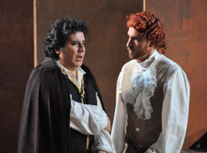 Des Grieux (Percy Martinez, left) learns that Lescaut (Nathan Matticks, right) has bribed a guard to free Manon from prison.