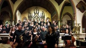 Choirmaster & Conductor Claudia Dumschat with singers & musician Photo by Judy Pantano